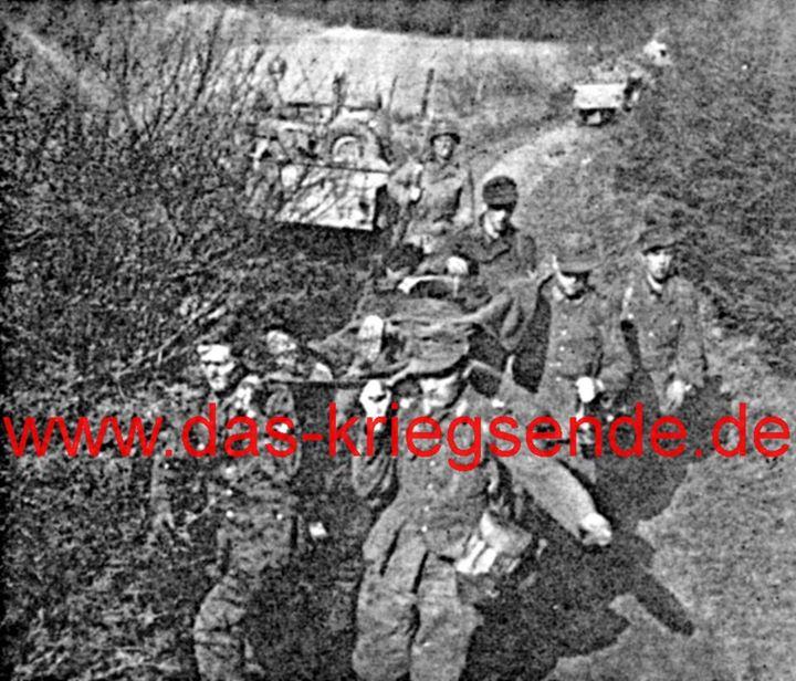 """Bild 11: 6. April 1945 - die Operation """"Neptune"""" hat begonnen und der Großangriff über die Sieg ist im Fortschreiten. Gefangene bringen Verwundete bei Gosenbach zur Gefangenensammelstelle."""