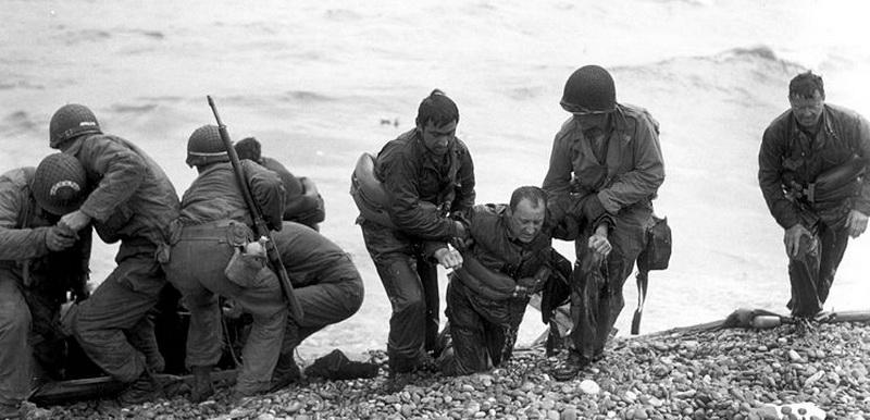 Amerikanische Infanterie hilft den Verwundeten am Strand in Sicherheit zu gelangen.  Foto US Signal Corps, Weintraub, Signature SC190366.