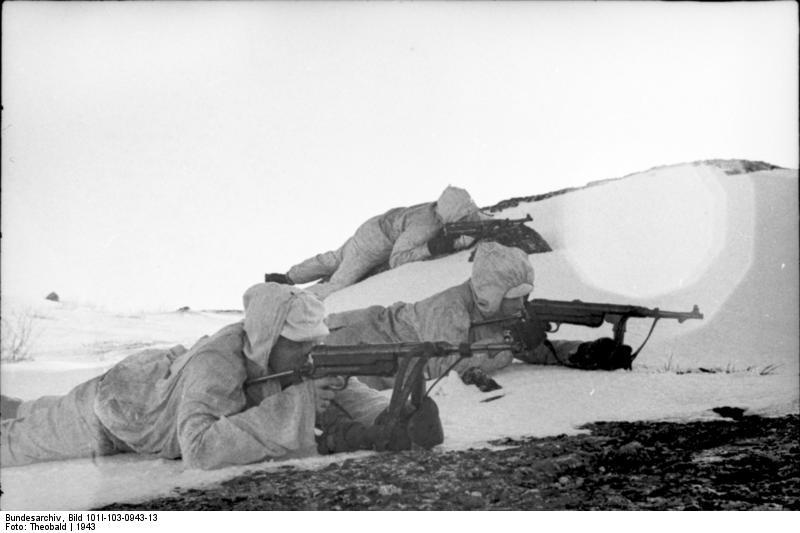 """Bild: Bundearchiv, Bild 101I-103-0943-13 """"Norwegen, Lappland, Finnland.- drei Soldaten (Gebirgsjäger?) mit Wintertarnanzügen mit Maschinenpistole in Deckung liegend; PK 680"""""""