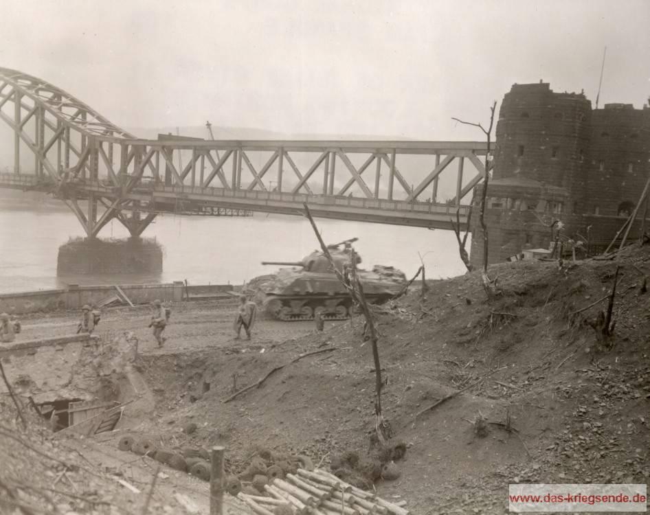Auf dem Ostufer des Rheins befinden sich Infanteriekräfte und ein Shermanpanzer auf dem Weg zur Front. Die Ludendorff-Brücke steht noch, demnach kann man das Foto vor den 17. März 1945 datieren. Vorne links im Bereich befindet sich ein ehemaliger Unterstand einer Flak-Stellung. Foto SIgnal-Corps, National-Archiv Washington, USA.