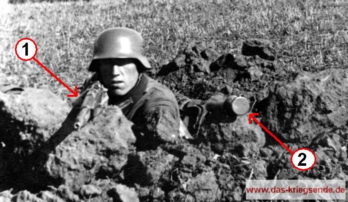 """Ein deutscher Grenadier ist in seiner Schützenmulde in Stellung gegangen. Mit seiner Feuerwaffe<span style=""""color: #ff0000;""""> (1)</span> im Anschlag und der bereitgelegten Stielhandgranate <span style=""""color: #ff0000;"""">(2)</span> erwartet er den bevorstehenden amerikanischen Angriff. Die Anspannung steht ihm erkennbar ins Gesicht geschrieben."""