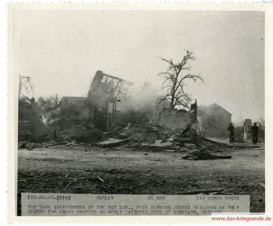 Am 25. März 1945 geht amerikanische Infanterie behutsam vor auf der Suche nach Heckenschützen in dem schwer geschädigten Uckerath. Der Kriegsberichterstatter Hurley vom Signal Corps der US Armee hat die Szenerie im Bild festgehalten.